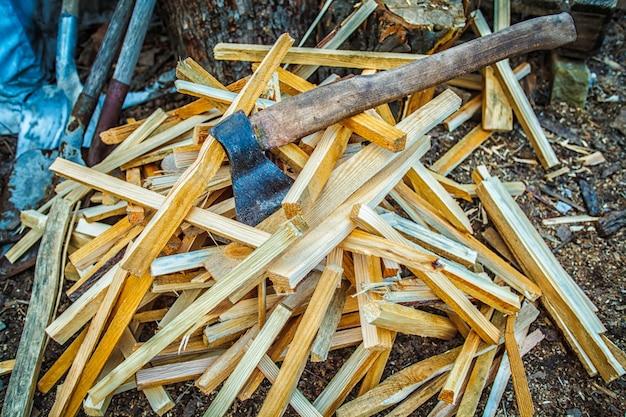 Machado velho no bloco de madeira com a pilha dos logs desbastados que encontram-se na terra.