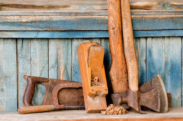 Machados, aparas de plaina e vi o antigo fundo de madeira azul