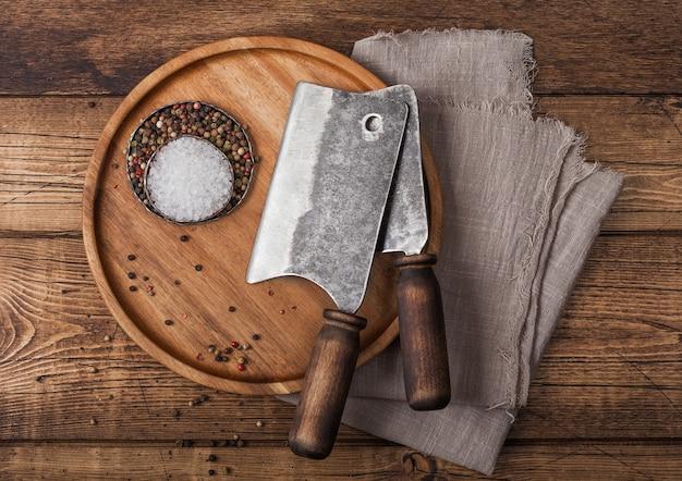 Machados vintage para carne na placa de madeira redonda com sal e pimenta no fundo de madeira com toalha de linho.