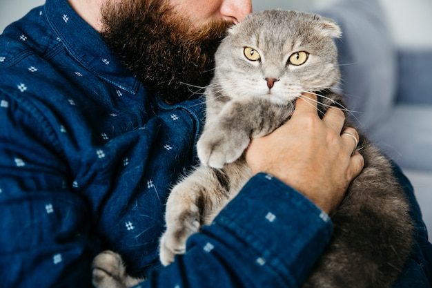 Macho abraçando gato adorável