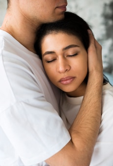 Macho abraçando namorada étnica com os olhos fechados