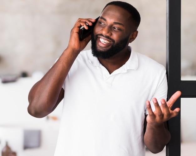 Macho adulto bonito falando ao telefone