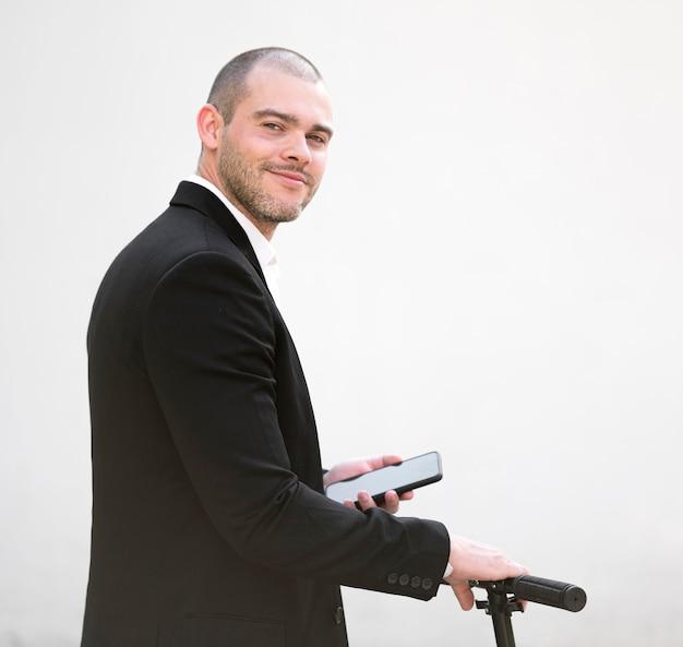 Macho adulto bonito feliz em andar de scooter