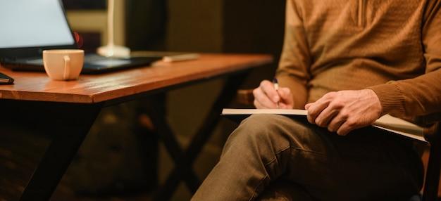 Macho adulto close-up, tomando notas de trabalho em casa