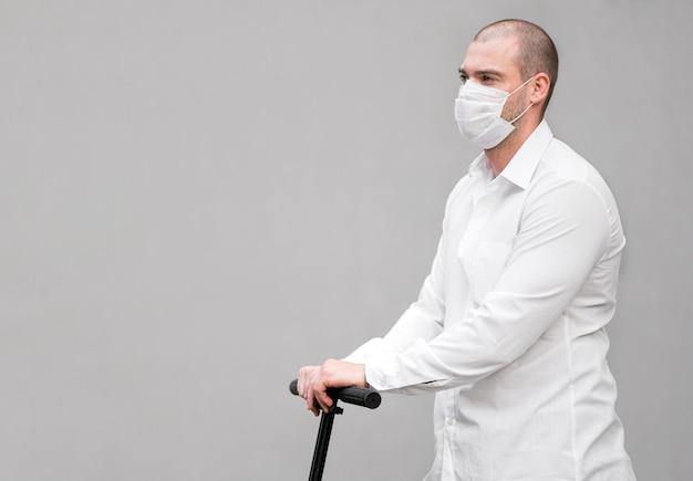 Macho adulto com máscara facial andando de scooter