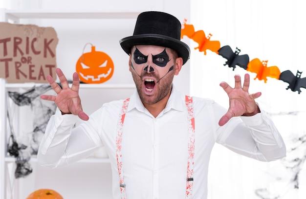 Macho adulto com rosto pintado para o halloween