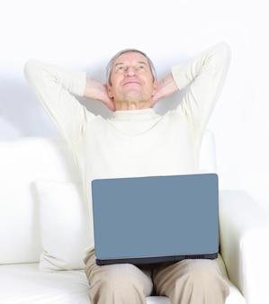 Macho adulto em casa descansando com um laptop.