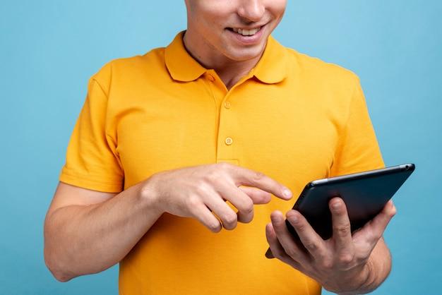 Macho adulto feliz navegando em um tablet