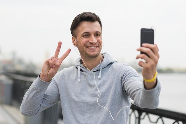 Macho adulto feliz tomando uma selfie