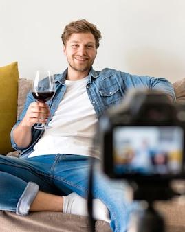 Macho adulto, gravando-se com copo de vinho