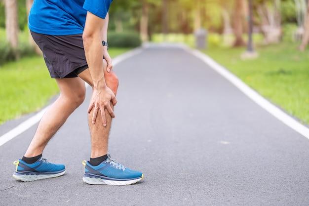 Macho adulto jovem com dores musculares durante a execução. o corredor tem dor no joelho devido à síndrome do joelho nos corredores ou da dor femoropatelar, osteoartrite e tendinite patelar. lesões esportivas e conceito médico
