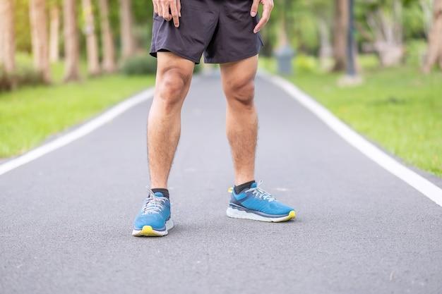 Macho adulto jovem em sapatos de esporte prontos para correr no parque ao ar livre, corredor homem correr e andar na estrada de manhã, músculos da perna do atleta. exercício, bem-estar, estilo de vida saudável e treino