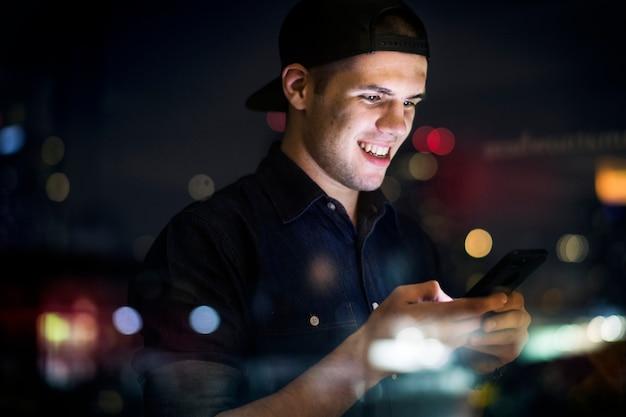 Macho adulto novo feliz que usa um smartphone em uma arquitectura da cidade da noite