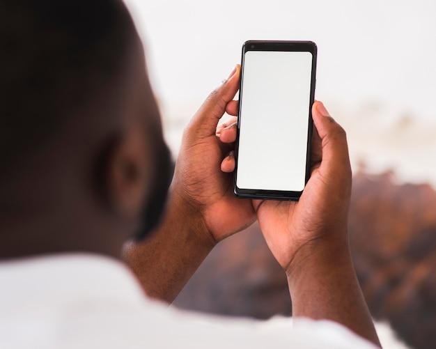 Macho adulto, segurando o telefone móvel