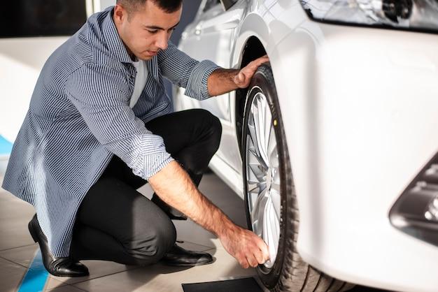 Macho adulto, verificando pneus de carro