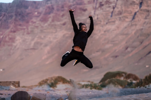 Macho afro-americano animado pulando na zona rural