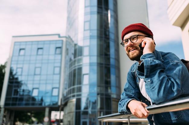 Macho alegre bonito jovem hipster barbudo falando no telefone e sorrindo. meio urbano, com espaço de cópia.