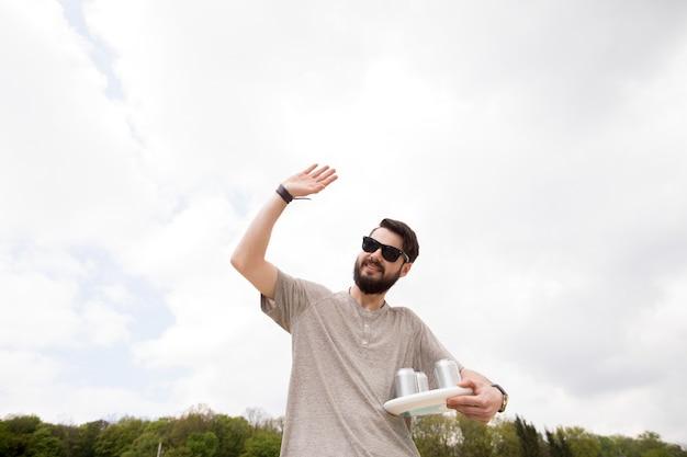 Macho alegre com bebidas acenando a mão