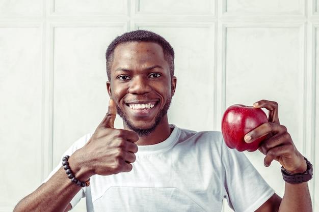 Macho americano africano saudável, segurando uma maçã