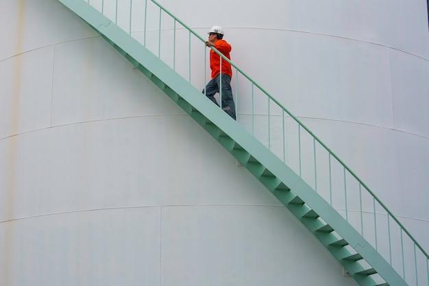 Macho andando na escada inspeção de óleo do tanque de armazenamento visual