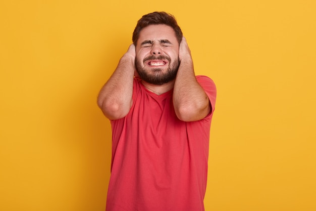 Macho barbudo bonito vestindo camiseta redcasual, homem atraente posando com ouvidos e olhos fechados, ouvir barulho alto, cara de pé isolado no amarelo. conceito de pessoas.