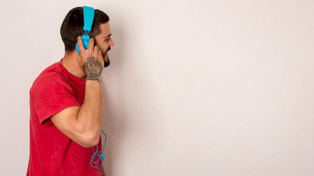 Macho barbudo escuta música com fones de ouvido