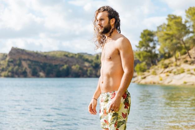 Macho barbudo jovem em pé perto do lago