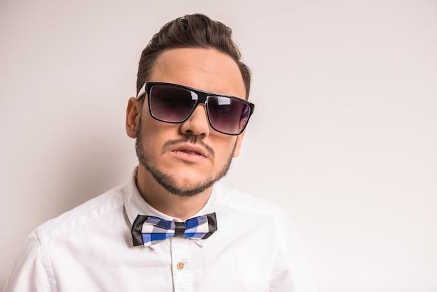 Macho bonito de óculos e gravata borboleta