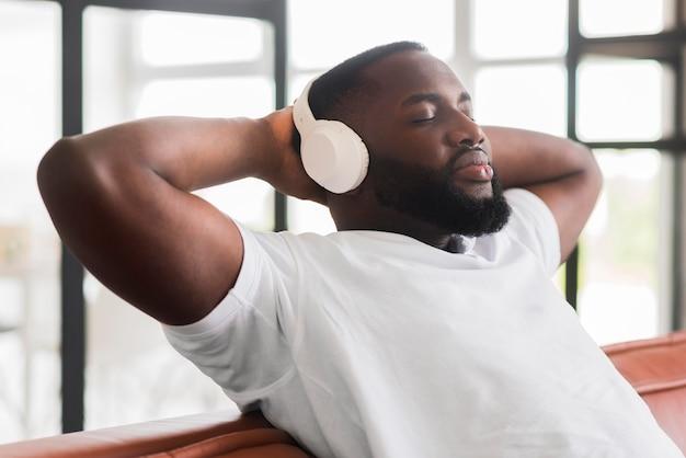 Macho bonito relaxante enquanto ouve música