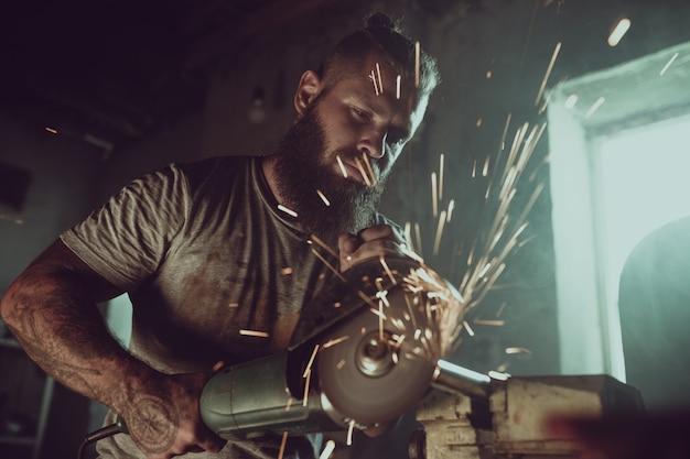 Macho brutal bonito com uma barba reparando uma motocicleta em sua garagem, trabalhando com uma serra circular. na garagem, muitas faíscas e fumaça de serrar