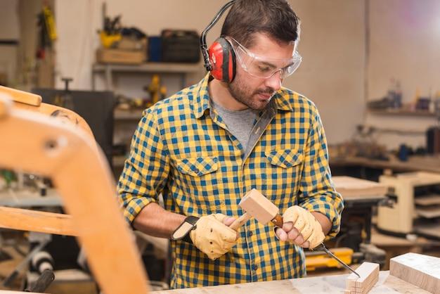 Macho carpinteiro segurando um martelo na mão batendo um formão no bloco de madeira