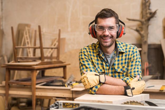 Macho carpinteiro usando óculos de segurança e defensor de orelha, apoiando-se na serra de mesa na oficina