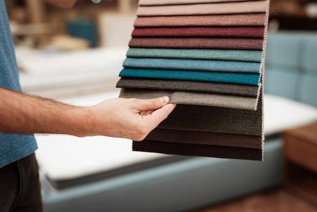 Macho cliente segurando amostras de têxteis multicoloridas