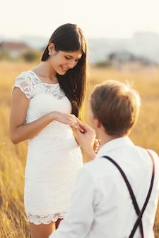 Macho colocando o anel de noivado na mão da mulher, ao ar livre em um dourado