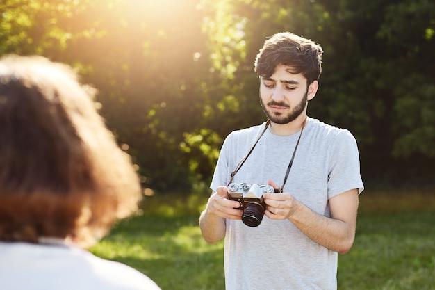 Macho com barba e penteado elegante, fazendo fotos de sua namorada, que está posando para a natureza, olhando fotos que ele conseguiu em sua câmera retro