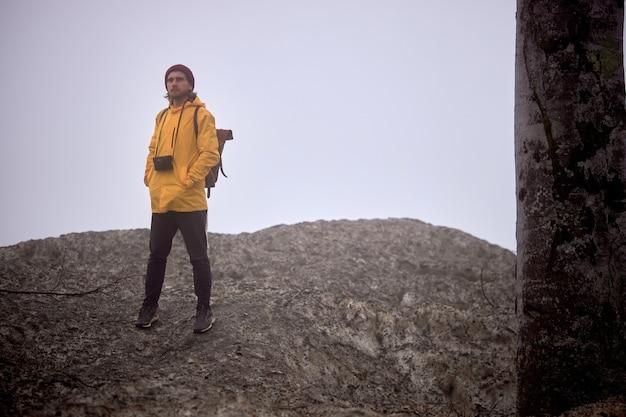 Macho com câmera descendo a montanha, em tempo nublado, sozinho