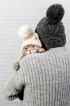 Macho com costas segurando gato com boné de pele