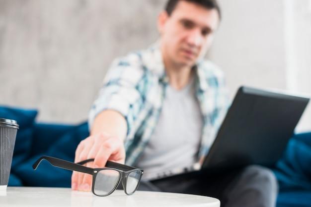 Macho com laptop colocar os óculos na mesa