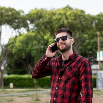 Macho com óculos de sol, comunicando-se com o smartphone
