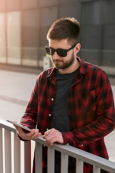 Macho com óculos de sol navegando smartphone
