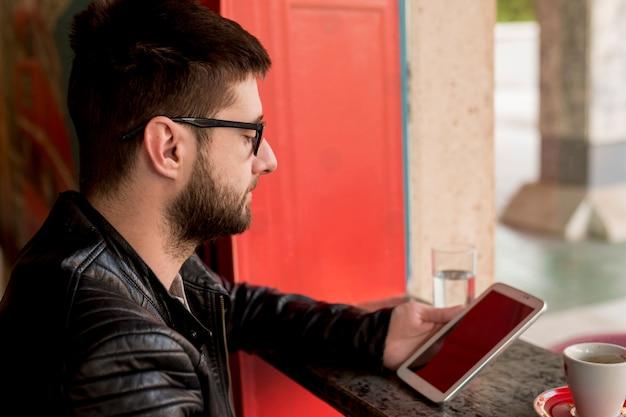 Macho com óculos de sol usando tablet