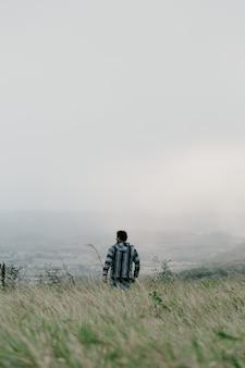 Macho com um casaco listrado, andando em um campo com grama alta perto do mar