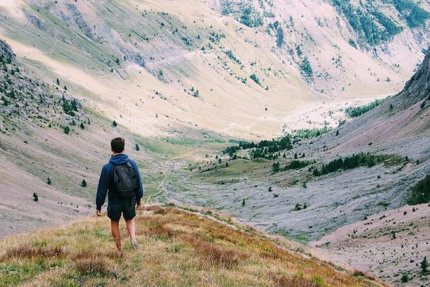 Macho com uma mochila em pé em um penhasco, apreciando a vista rodeada por montanhas, tiro por trás