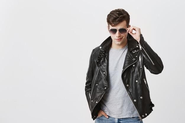 Macho confiante muscular posando dentro de casa. atraente bonitão caucasiano com corte de cabelo na moda na jaqueta de couro preta, segurando os óculos de sol na mão, olhando com apelo