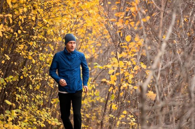Macho correndo na trilha na floresta