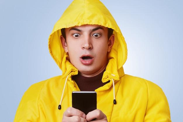 Macho de aparência agradável chocado olha para o telefone inteligente, verifica sua conta bancária on-line, percebe que não há dinheiro, tem que pagar muitas dívidas. homem surpreendido recebe mensagem chocada no dispositivo