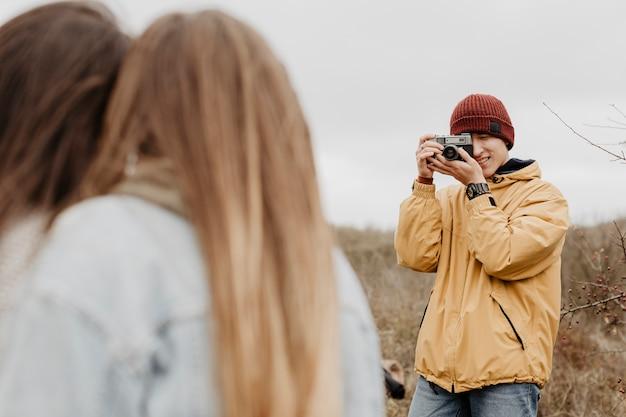 Macho de baixo ângulo, tirando fotos de mulheres
