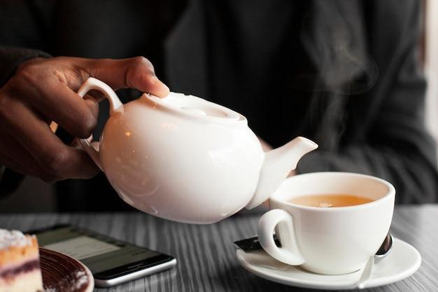 Macho de close-up, desfrutando de uma xícara de chá