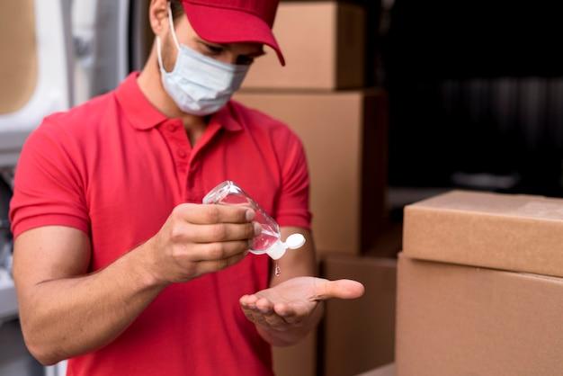 Macho de entrega usando desinfetante para as mãos