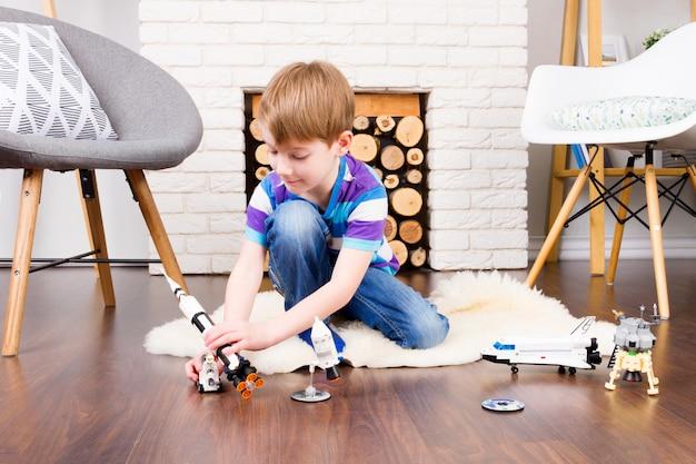 Macho de menino criança brincando com o construtor de brinquedos do cosmos: boneca de foguete, ônibus, rover, satélite e astronauta no interior confortável em casa, no piso de madeira